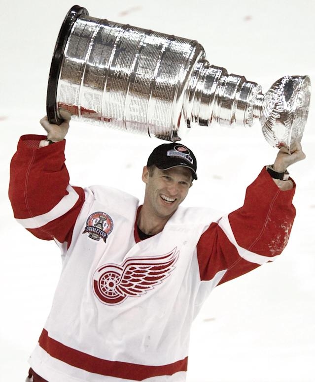 FILE - In this June 13, 2002 file photo, Detroit Red Wings goalie Dominik Hasek, of the Czech Republic, carries the Stanley Cup after defeating the Carolina Hurricanes 4-1 games in Detroit. Hasek, Mike Modano, Peter Forsberg and Rob Blake are headed into the Hockey Hall of Fame. The four players were among six selected Monday, June 23, 2014 for induction in November. (AP Photo/Paul Sancya, file)