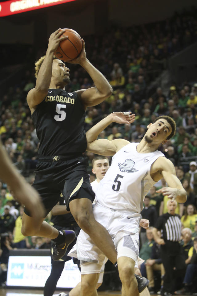 Colorado's D'Shawn Schwartz, left, shoots over Oregon's Chris Duarte during the second half of an NCAA college basketball game in Eugene, Ore., Thursday, Feb. 13, 2020. (AP Photo/Chris Pietsch)