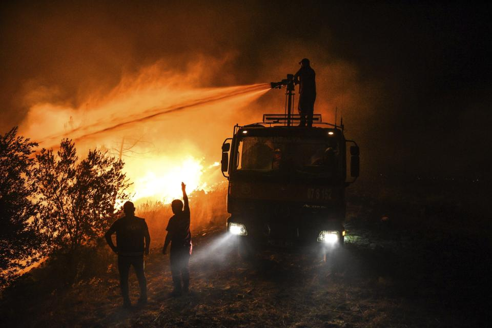 Firefighters pour water as they try to get the fire under control in Kirli village near the town of Manavgat, in Antalya province, Turkey, early Friday July 30, 2021. The fire that continued all night could not be brought under control and people living in the village started to evacuate. Wildfires are common in Turkey's Mediterranean and Aegean regions during the arid summer months, although some previous forest fires have been blamed on arson. (AP Photo)