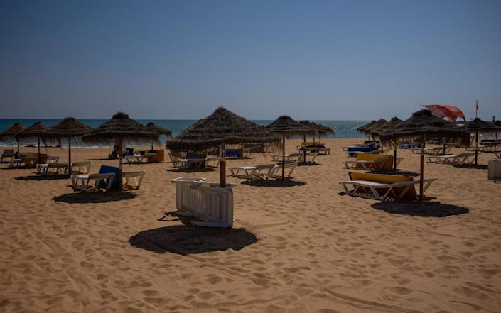 Empty sun loungers sit on the sand at Villamoura beach in Portugal's Algarve - BLOOMBERG