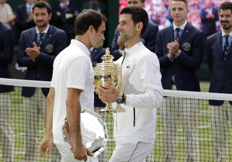 FILE - In this July 14, 2019, file photo, second placed Switzerland's Roger Federer, left, walks past winner Novak Djokovic, of Serbia, during trophy ceremonies after the men's singles final match at the Wimbledon Tennis Championships in London. (AP Photo/Ben Curtis, File)