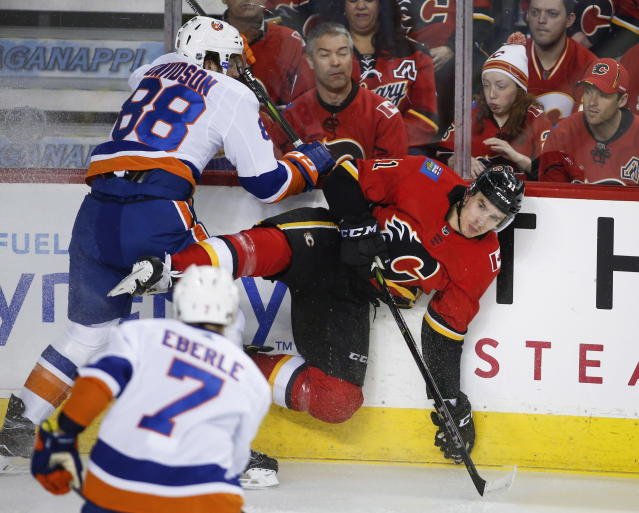New York Islanders' Brandon Davidson, left, checks Calgary Flames' Mikael Backlund, from Sweden, during first period NHL hockey action in Calgary, Alberta, Sunday, March 11, 2018. (Jeff McIntosh/The Canadian Press via AP)