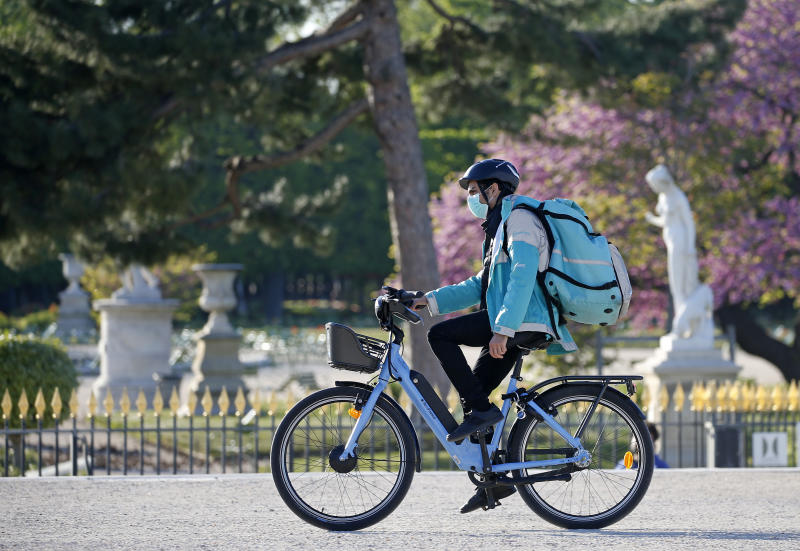 A deliveryman for Deliveroo wearing a protective mask rides his bike. Photo: Chesnot/Getty Images