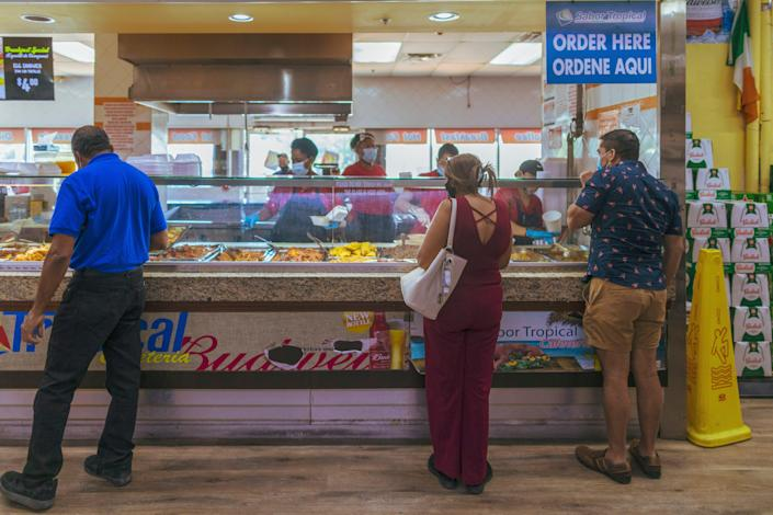 Elsa Romero waits in line to buy lunch at a supermarket March 16 in Miami.