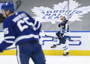 Winnipeg Jets left wing Kyle Connor (81) celebrate his goal as Toronto Maple Leafs right wing Ilya Mikheyev (65) skates by during second period NHL hockey action in Toronto on Monday, Jan. 18, 2021. (Nathan Denette/The Canadian Press via AP)