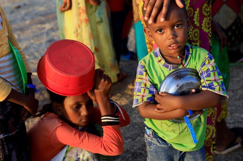 An Ethiopian child who fled war in Tigray region, carries his plate as he queues for wet food ration at the Um-Rakoba camp, on the Sudan-Ethiopia border in Al-Qadarif state