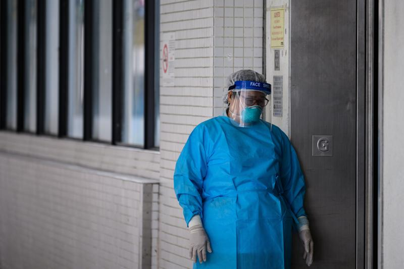 A medical worker wearing protective gear stands outside a lift in the grounds of Princess Margaret Hospital in Hong Kong on February 4, 2020. - Hong Kong on February 4 became the second place outside mainland China to report the death of a coronavirus patient as officials said they feared local transmissions were increasing in the densely populated city. (Photo by Anthony WALLACE / AFP) (Photo by ANTHONY WALLACE/AFP via Getty Images)