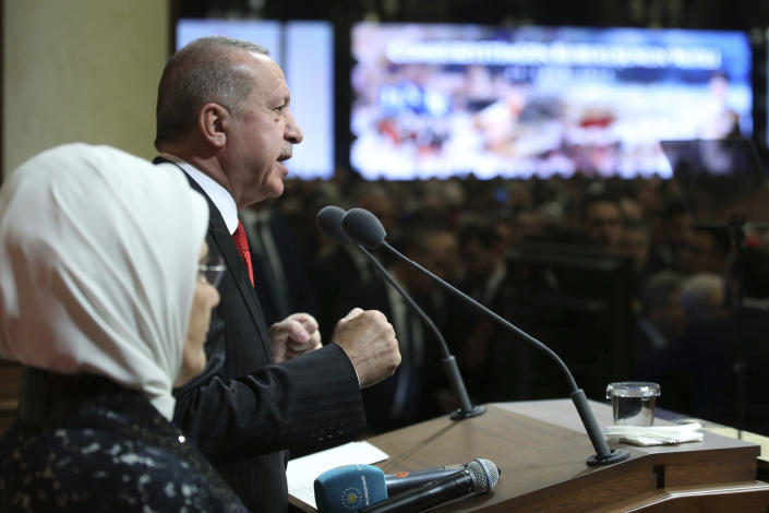 """Turkish President Recep Tayyip Erdogan is flanked by his wife Emine Erdogan as he speaks during a reception on Republic Day, in Ankara, Turkey, Tuesday, Oct. 29, 2019. Erdogan said Russia has informed Turkey that Syrian Kurdish fighters have """"completely been removed"""" from the areas in northeast Syria. (Presidential Press Service via AP, Pool)"""