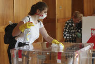 A member of an electoral commission, wearing a mask and gloves for protection against the coronavirus, uses a disinfectant to clean the voting box, in line with sanitary requirements, during presidential election in Poland held in the COVID-19 pandemic, in Warsaw, Poland, Sunday, June 28, 2020. (AP Photo/Czarek Sokolowski)