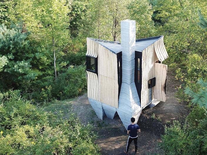 Drone photo of cabin in forest landscape.