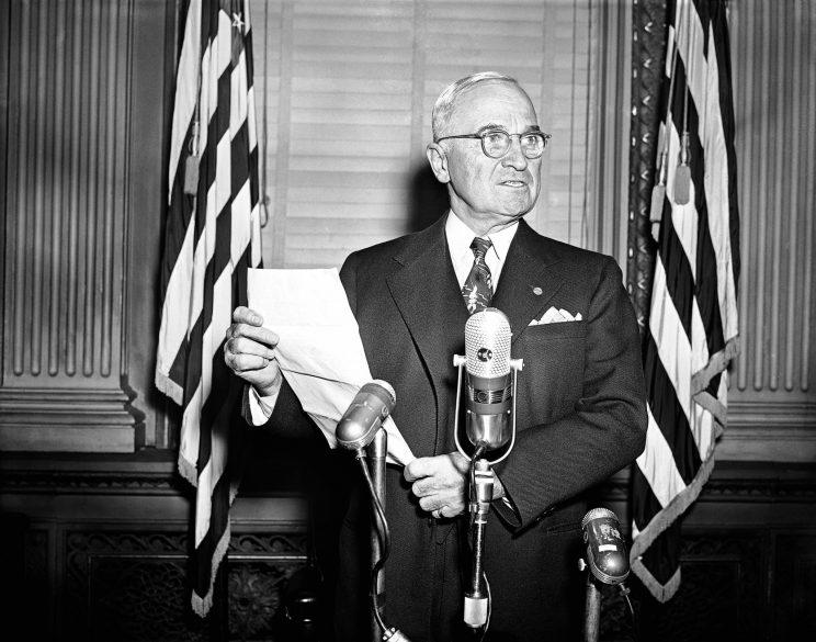 President Harry S. Truman repeats for cameramen (who were excluded at the news session) his warning that U.N. forces would not back down in Korea and the atom bomb would be used if necessary to meet the military situation. The re-enactment was in the same executive office room in Washington, Nov. 30, 1950 where his press conferences are held. (Photo: Henry Griffin/AP)