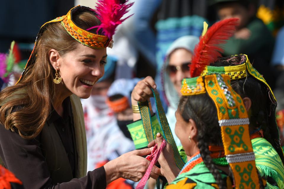 TOPSHOT - Britain's Catherine (L), Duchess of Cambridge, receives gifts from a member of the Kalash tribe during her visit to theBumburate Valley in Pakistan northern Chitral District on October 16, 2019. - Prince William and his wife Kate flew near the Afghan border to visit a remote Hindu Kush glacier on October 16, after a morning spent trying on feathered traditional caps and luxurious shawls in Pakistan's mountainous north. (Photo by FAROOQ NAEEM / AFP) (Photo by FAROOQ NAEEM/AFP via Getty Images)