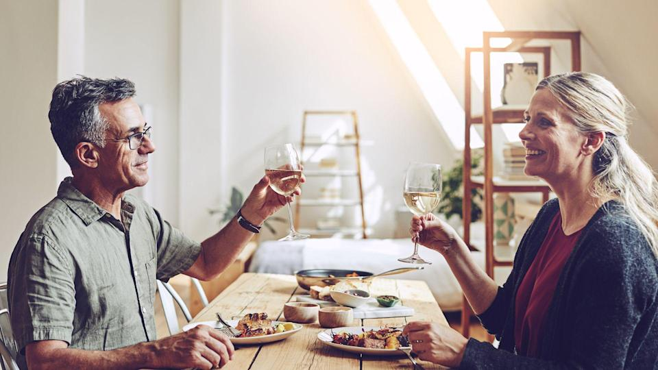 Shot of a mature couple having a meal by the dining room table at home.