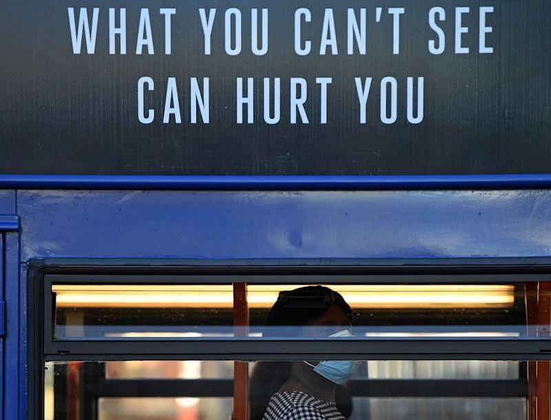 """A woman wearing a face mask or covering due to the COVID-19 pandemic, sits beneath a sign reading """"What you can't see, Can hurt you"""", as she travels by bus in Manchester, northwest England - OLI SCARFF / AFP"""