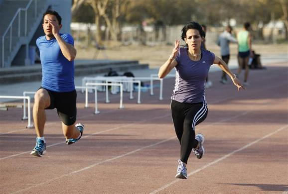 Iraqi sprinter Dana Abdul-Razzaq (R) during a training session in Baghdad University, February 27, 2012.