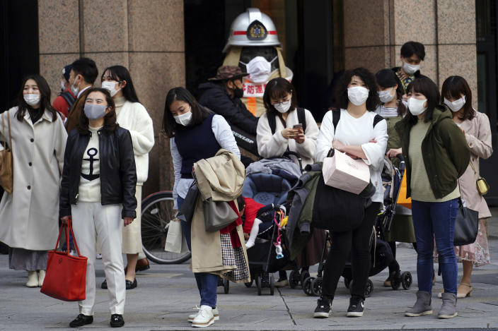 People wearing protective masks to help curb the spread of the coronavirus wait for a traffic light at an intersection Monday, March 1, 2021, in Tokyo. The Japanese capital confirmed more than 120 new coronavirus cases on Monday. (AP Photo/Eugene Hoshiko)