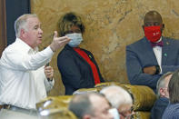 Sens. Sarita Simmons, D-Cleveland, center and Derrick Simmons, D-Greenville, right, listen as Rep. Mark Tullos, R-Raleigh, asks a question during discussion on the bill to change the Mississippi state flag Sunday, June 28, 2020 at the Capitol in Jackson, Miss. The bill passed 92-23 and the legislation headed to the Senate for their consideration. The current flag has in the canton portion of the banner the design of the Civil War-era Confederate battle flag, that has been the center of a long-simmering debate about its removal or replacement. (AP Photo/Rogelio V. Solis)