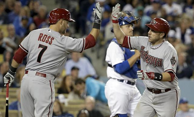 Arizona Diamondbacks' Miguel Montero, right, celebrates his home run past Los Angeles Dodgers catcher Tim Federowicz with Cody Ross during sixth inning of a baseball game in Los Angeles, Friday, April 18, 2014. (AP Photo/Chris Carlson)