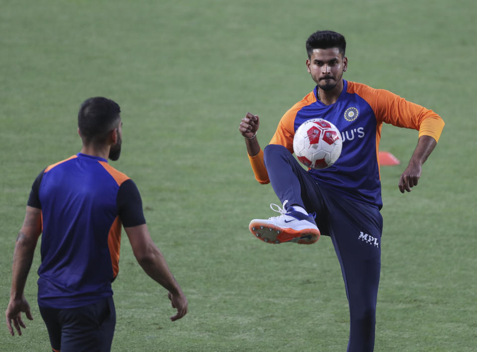 India's Shreyas Iyer, right, warms up with a soccer ball warm up during a training session ahead of the first Twenty20 cricket match between India and England in Ahmedabad, India, Monday, March 8, 2021. (AP Photo/Aijaz Rahi)