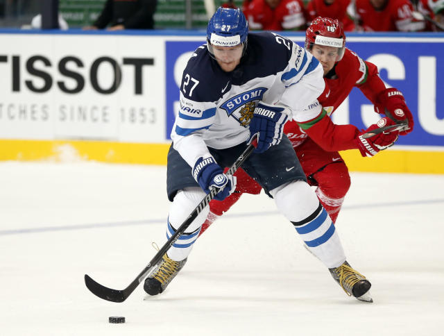 Finland forward Petri Kontiola, left, battles for the puck with Belarus forward Geoff Platt during the Group B preliminary round match between Finland and Belarus at the Ice Hockey World Championship in Minsk, Belarus, Thursday, May 15, 2014. (AP Photo/Darko Bandic)