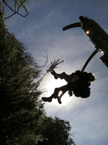 This photo provided by Los Angeles County Search and Rescue Reserve Deputy Doug Cramoline shows the helicopter rescue of Kyndall Jack, 18, by an L.A. County deputy after being missing for five days in rugged country near Rancho Santa Margarita, Calif., Thursday, April 4, 2013. A rescue team followed the sounds of a screaming female voice to an almost vertical canyon wall where they found Jack clinging to a rocky outcropping after going missing during a last Sunday. (AP Photo/L.A. County Search and Rescue Reserve, Deputy Doug Cramoline)