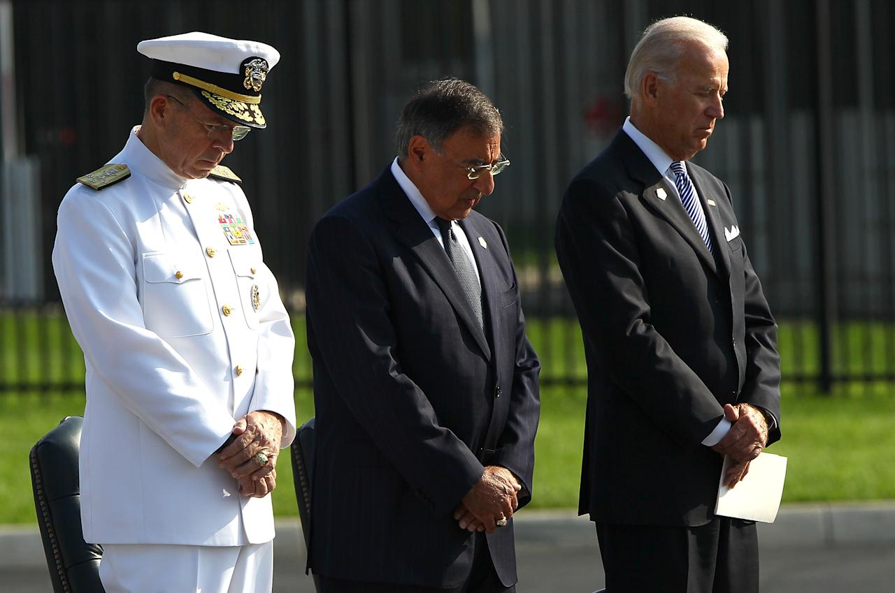 (L-R) Chairman of the Joint Chiefs of Staff Michael Mullen, Secretary of Defense Leon Panetta, and Vice President Joe Biden observe a moment of silence during the time of impact at a remembrance ceremony at the Pentagon September 11, 2011 in Arlington, Virginia. The United States is commemorating the 10th anniversary of the terrorist attacks of September 11, 2001 which resulted in the deaths of 2,753 people when two hijacked planes crashed into the World Trade Center. Security has been heightened in both New York City and Washington D.C. following a terrorist threat about a car bomb.  (Photo by Win McNamee/Getty Images)