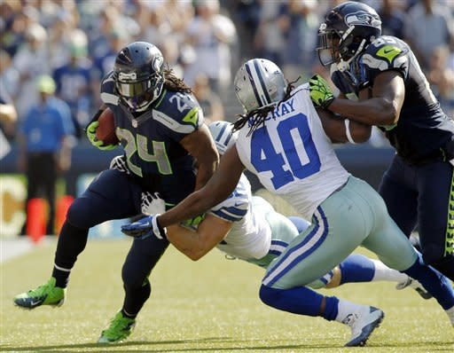 Seattle Seahawks' Marshawn Lynch is hit by Dallas Cowboys' Dan Connor, rear, and Danny McCray as Seahawks' Anthony McCoy blocks in the second half of an NFL football game, Sunday, Sept. 16, 2012, in Seattle. The Seahawks won 27-7. (AP Photo/John Froschauer)