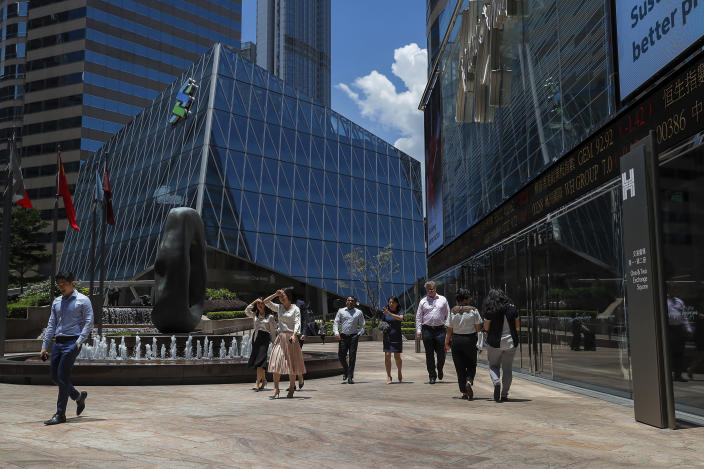 Office workers walk past an electronic board showing shares prices at the financial district in Hong Kong, Monday, Aug. 5, 2019. Asian stock markets fell for a third day Monday after China allowed its yuan to sink to its lowest level this year following President Donald Trump's latest tariff threat. (AP Photo/Kin Cheung)