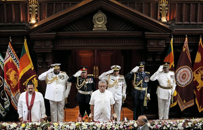Sri Lanka's President Gotabaya Rajapaksa and his brother and former leader Mahinda Rajapaksa, who was appointed as the new Prime Minister, stand for national anthem during the swearing in ceremony in Colombo