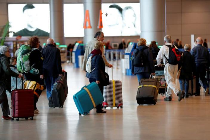 Travelers walk with their suitcases in the departures terminal after Israel said it will require anyone arriving from overseas to self-quarantine for 14 days as a precaution against the spread of coronavirus, at Ben Gurion in Lod, near Tel Aviv
