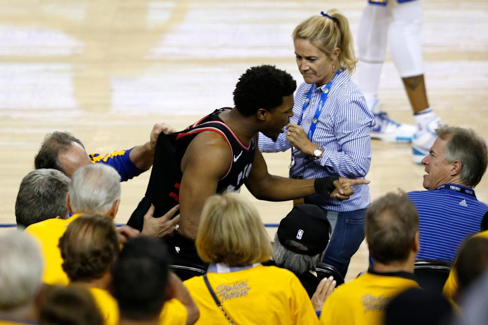 Kyle Lowry of the Toronto Raptors argues with Warriors minority owner Mark Stevens (blue shirt) after Lowry chased down a loose ball in the second half against the Golden State Warriors during Game 3 of the 2019 NBA Finals at Oracle Arena.