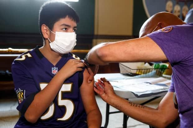 Dr. Barry Lavallee, CEO of Keewatinowi Inniniw Minoayawin, administers the Pfizer-BioNTech vaccine to Alexander Herrera, 14, at the Aboriginal Health and Wellness Centre in Winnipeg on Monday (Mike Deal/Winnipeg Free Press/The Canadian Press - image credit)