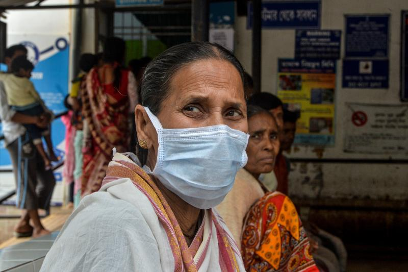 An elderly woman wearing a protective facemask sits with other patients coming to the outdoor patient department (OPD) for an awareness event about the COVID-19 coronavirus and other airborne diseases at the Siliguri District Government hospital in Siliguri on February 21, 2020. (Photo by DIPTENDU DUTTA / AFP) (Photo by DIPTENDU DUTTA/AFP via Getty Images)