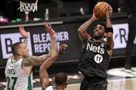 Brooklyn Nets guard Kyrie Irving (11) shoots over Boston Celtics center Daniel Theis during the first half of an NBA basketball game, Thursday, March 11, 2021, in New York. (AP Photo/Adam Hunger)