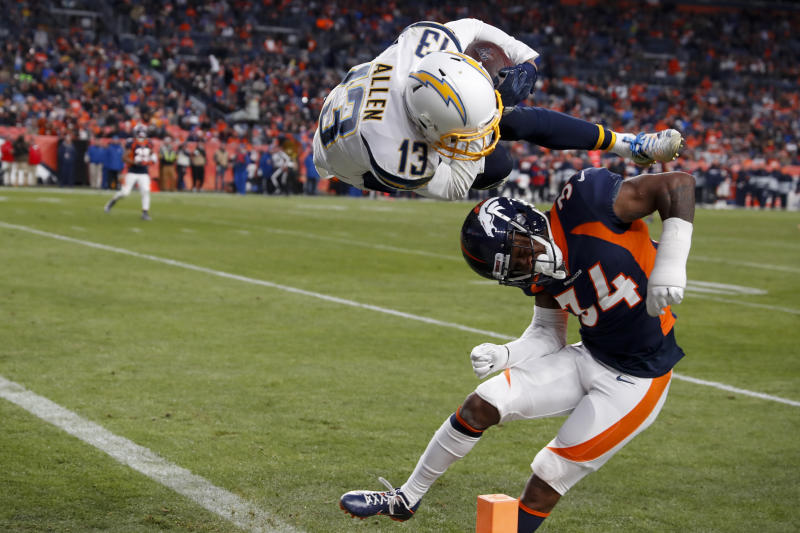 Los Angeles Chargers wide receiver Keenan Allen scores over Denver Broncos strong safety Will Parks during the second half of an NFL football game Sunday, Dec. 1, 2019, in Denver. (AP Photo/David Zalubowski)