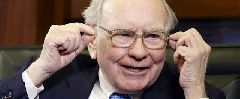 Warren Buffett smiling and gesturing with both hands