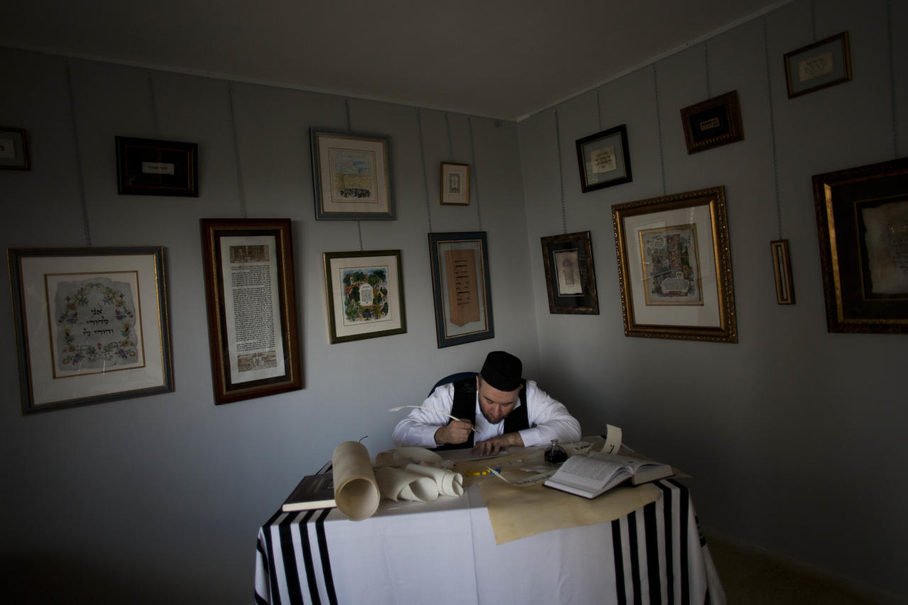 In this Tuesday, Jan. 17 2012 photo, calligraphy expert Avraham Borshevsky practices at his studio in Jerusalem. In a world overwhelmed by electronic gadgets that have changed the way we read, write and learn, the Jewish and Islamic arts of calligraphy have preserved their methods for generations. (AP Photo/Bernat Armangue)