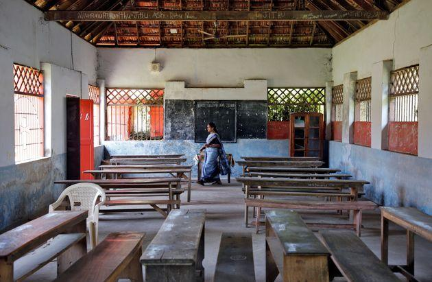 A staff member walks inside an empty classroom of a school after Kerala government ordered the closure of schools across the state, March 12, 2020.