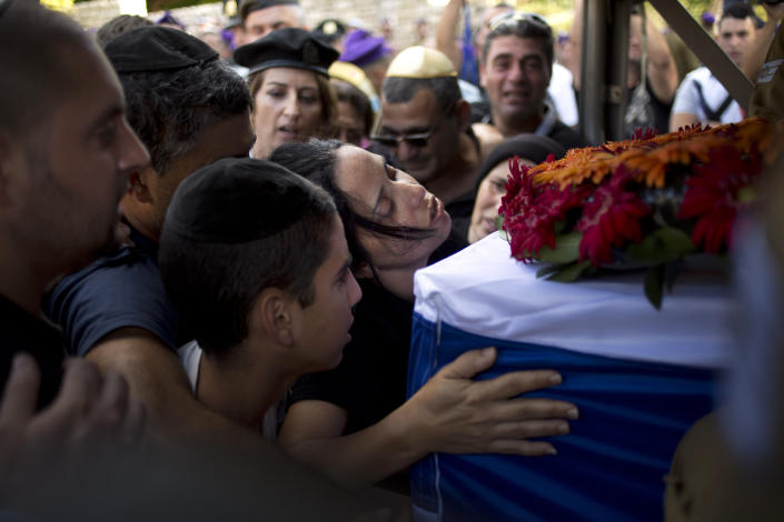Smadar, mother of Israeli soldier, Staff Sergeant Gabriel Koby, mourns overs his coffin during his funeral at the military cemetery in Haifa , Israel, Monday, Sept. 23, 2013. Koby, 20, was shoot and killed by an unknown gunmen in the biblical city of Hebron in the West Bank on Sunday, and troops are searching for the shooter, the military said. It was the second soldier killed since the weekend when a Palestinian killed an Israeli soldier with the intention of trading the body for his brother who is jailed for shooting attacks. (AP Photo/Ariel Schalit)