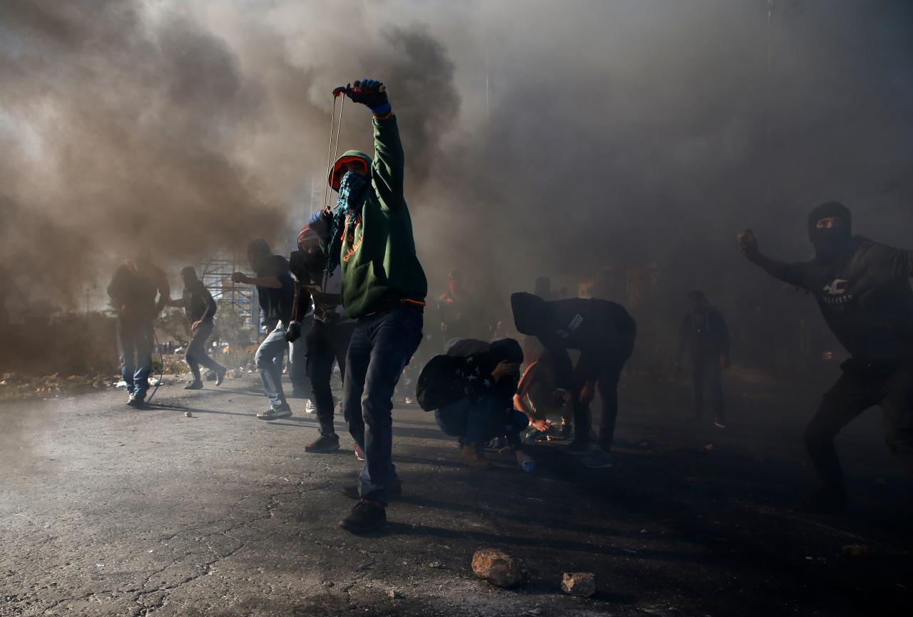 <p>Palestinian protesters clash with Israeli troops near an Israeli checkpoint in the West Bank city of Ramallah on Dec. 8, 2017. (Photo: Abbas Momani/AFP/Getty Images) </p>