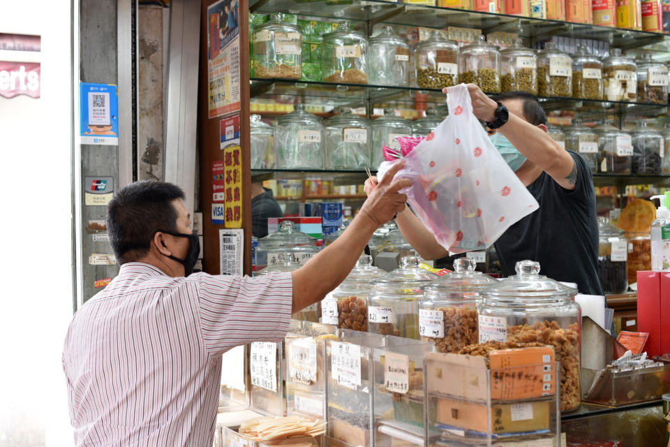 A man wearing a face mask receives a plastic bag with traditional Chinese medicinal products being sold at a Chinese medical hall in Singapore's Chinatown district on Tuesday, May 12, 2020. Singapore has allowed selected businesses such as traditional Chinese medicine medical halls, home-based establishments, food manufacturing, selected food retail outlets, laundry services, traditional barbers and pet supplies to reopen May 12 in a cautious rollback of a two-month partial lockdown to curb the spread of COVID-19 infections in the city-state. (AP Photo/YK Chan)