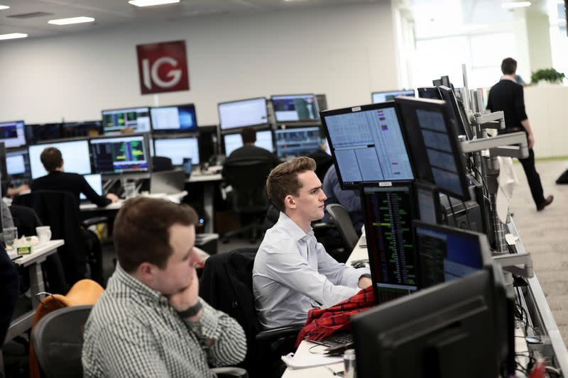 Traders look at financial information on computer screens on the IG Index trading floor