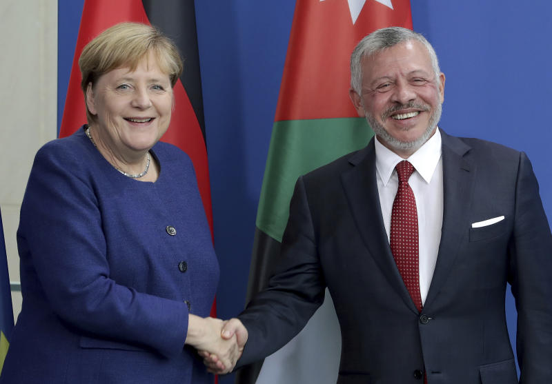 German Chancellor Angela Merkel, left, and Jordan's King Abdullah II, right, shake hands after a joint press conference as part of a meeting at the Chancellery in Berlin, Germany, Tuesday, Sept. 17, 2019. (AP Photo/Michael Sohn)