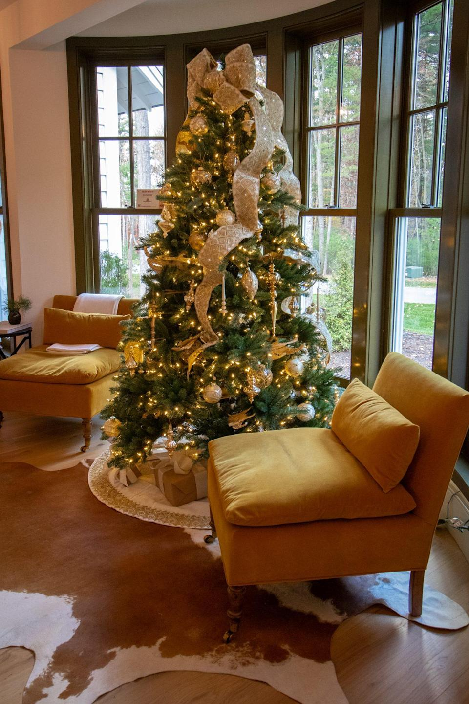 """<p>A Biltmore spruce from <a href=""""https://www.balsamhill.com/c/christmas-at-the-biltmore-decorating-theme"""" rel=""""nofollow noopener"""" target=""""_blank"""" data-ylk=""""slk:Balsam Hill"""" class=""""link rapid-noclick-resp"""">Balsam Hill</a> twinkles in the bay window of the sitting room. Metallic ornaments from the <a href=""""https://www.balsamhill.com/p/biltmore-legacy-ornament-set?sku=4002553"""" rel=""""nofollow noopener"""" target=""""_blank"""" data-ylk=""""slk:Biltmore Legacy Ornament Set"""" class=""""link rapid-noclick-resp"""">Biltmore Legacy Ornament Set</a> and a sparkly ribbon cascading from the top help the tree really shine. </p>"""