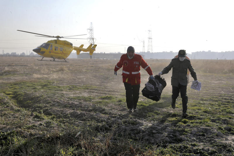 Rescue workers carry items retrieved from the scene where a Ukrainian plane crashed in Shahedshahr, southwest of the capital Tehran, Iran, Wednesday, Jan. 8, 2020. A Ukrainian airplane with more than 170 people crashed on Wednesday shortly after takeoff from Tehran's main airport, killing all onboard. (AP Photo/Ebrahim Noroozi)