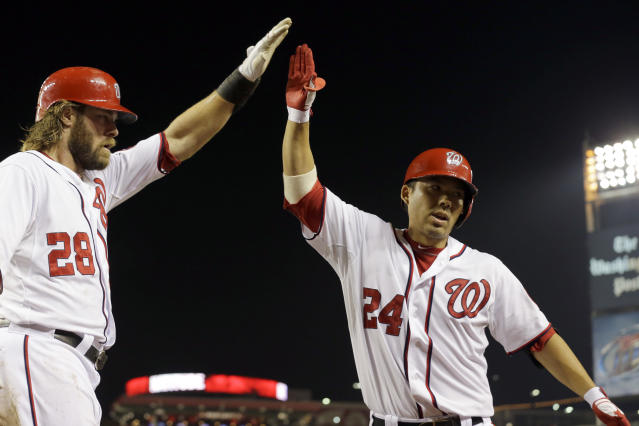FILE - In this Aug. 13, 2013, file photo, Washington Nationals' Jayson Werth (28) celebrates with Kurt Suzuki (24), after Suzuki's sacrifice fly scored Werth during the eighth inning of a baseball game against the San Francisco Giants, at Nationals Park in Washington. Catcher Kurt Suzuki is heading back to the Washington Nationals after agreeing to a $10 million, two-year contract, a deal pending a successful physical. The deal was disclosed to The Associated Press on Monday, Nov. 19, 2018, by a person familiar with the agreement who spoke on condition of anonymity because the contract was not yet official. (AP Photo/Alex Brandon, File)