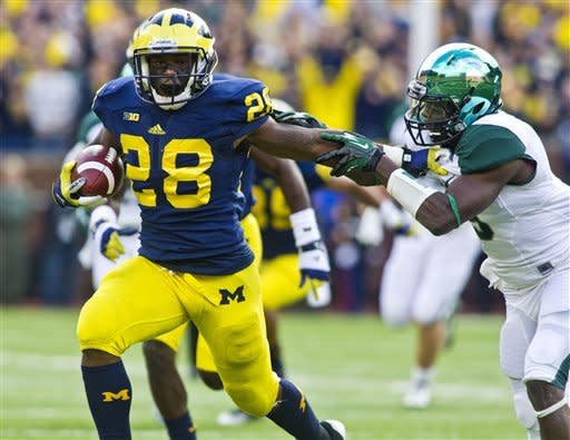 Michigan running back Fitzgerald Toussaint (28) holds back Michigan State safety Isaiah Lewis (9) during the second quarter of an NCAA college football game, Saturday, Oct. 20, 2012, in Ann Arbor, Mich. (AP Photo/Tony Ding)
