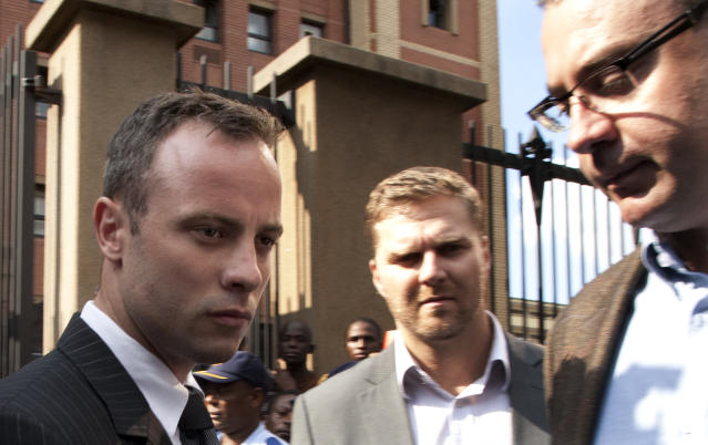 Oscar Pistorius, accompanied by relatives, leaves the high court in Pretoria, South Africa, Tuesday, March 18, 2014. Pistorius is charged with murder for the shooting death of his girlfriend, Reeva Steenkamp, on Valentines Day in 2013. (AP Photo/Themba Hadebe)