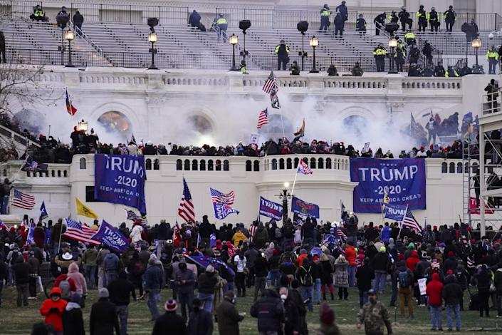"""Clouds of tear gas smoke hover over a mob as it storms the U.S. Capitol waving blue """"Trump 2020"""" banners."""