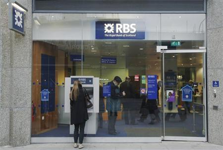 A woman stands in front of a Royal Bank of Scotland cash machine, in central London